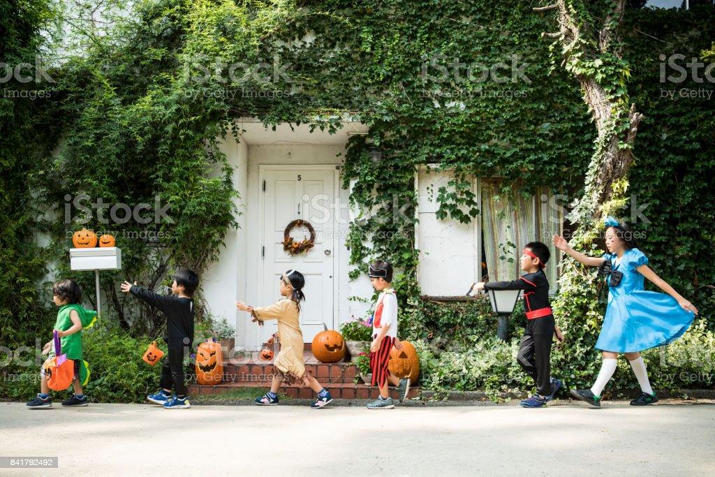 子供たちの衣装を着て家の前に行進しています。 ストックフォト