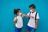 istock Children meet and greet each other with elbows while wearing surgical face mask for coronavirus 1286723189