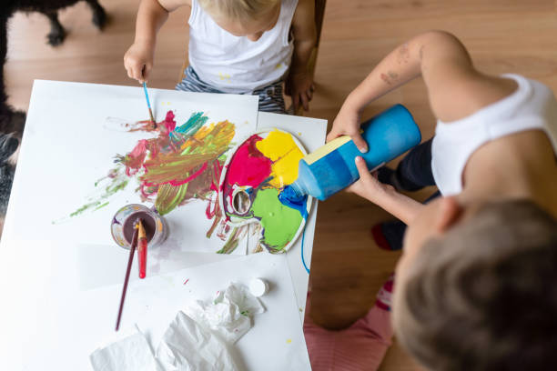 Children mixing colorful paints while painting stock photo
