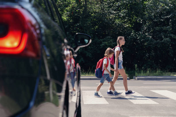 Children next to a car walking through pedestrian crossing to the school stock photo