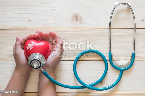 istock Children nursing pediatric care concept with kid patient's hands supporting red heart with medical doctor's stethoscope 954517600