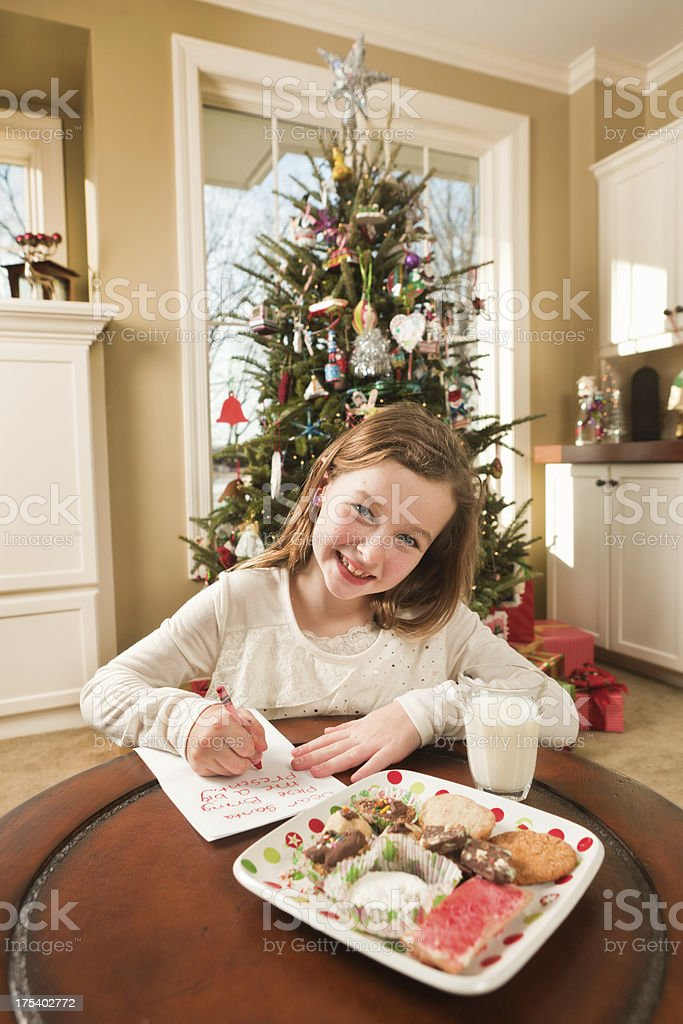 Young children girl with santa\'s milk and cookies, writing a...