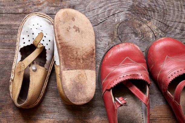 Crianças sapatos velhos de moda em madeira vintage de fundo de fundo. Lembrete da infância - foto de acervo