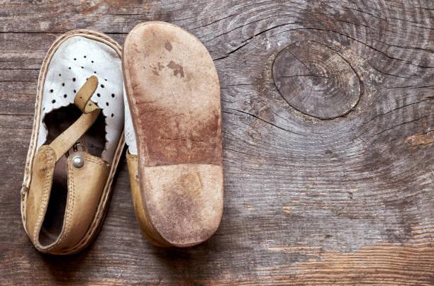 Crianças sapatos velhos de moda em fundo de madeira vintage de cima - foto de acervo
