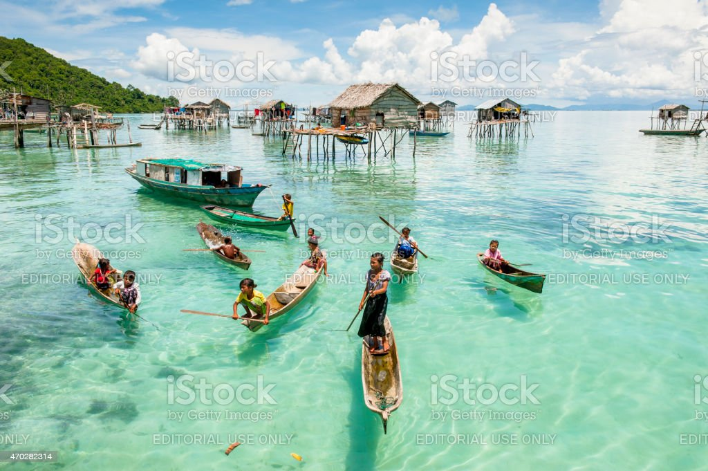 Children on boat above clear sea water, Malaysia stock photo
