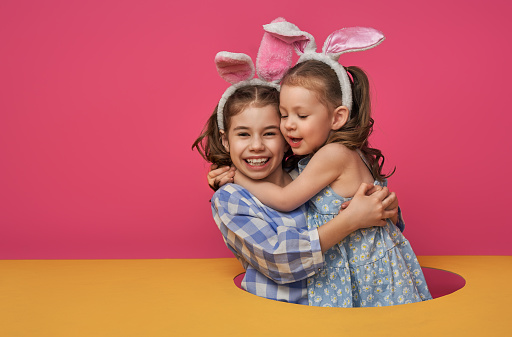 Two cute little children are wearing bunny ears at Easter day. Sisters girls on pink and yellow background.