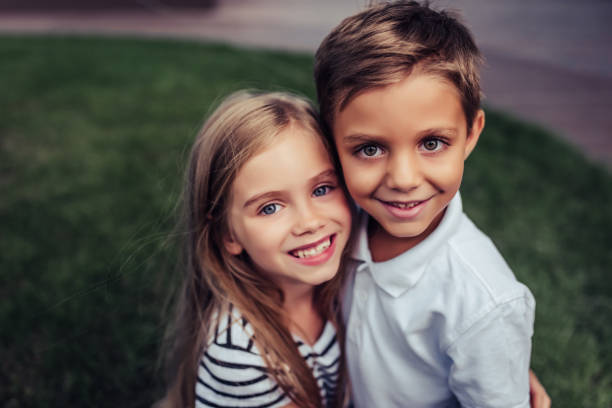Children on green grass Couple of charming childs having fun outdoors. Portrait of beautiful girl and boy are hugging, smiling and looking at the camera. Little brother and sister in park on a green grass. sibling stock pictures, royalty-free photos & images