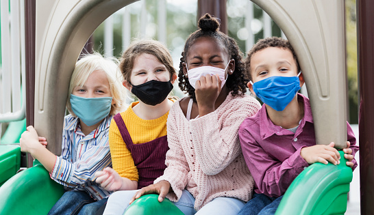 A multi-ethnic group of four children, 5 to 7 years old, playing together on a playground during school recess. They are sitting side by side on two slides, looking at the camera. They are all wearing masks, back to school during the COVID-19 pandemic, trying to prevent the spread of coronavirus.