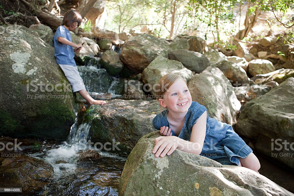 Children on rocks by river 免版稅 stock photo