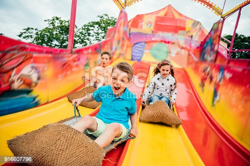 Children having fun sliding down a yellow and red slide while sitting in  burlap sacks