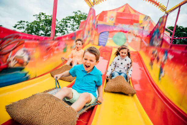 children on slide at a funfair - carnival stock photos and pictures