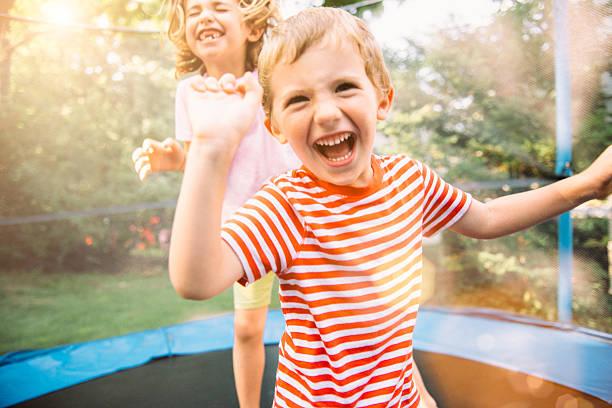 niños en vacaciones de verano salto sobre trampolín - trampolín artículos deportivos fotografías e imágenes de stock