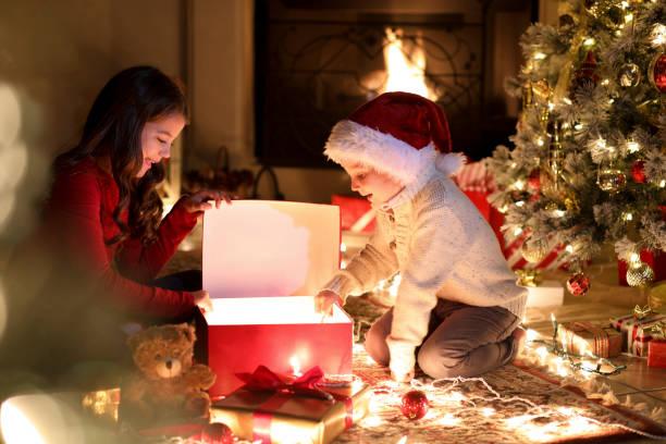 Children open presents during Christmas season near tree. stock photo