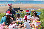 A candid photograph of children having fun and opening presents at a Christmas party on the beach in New Zealand