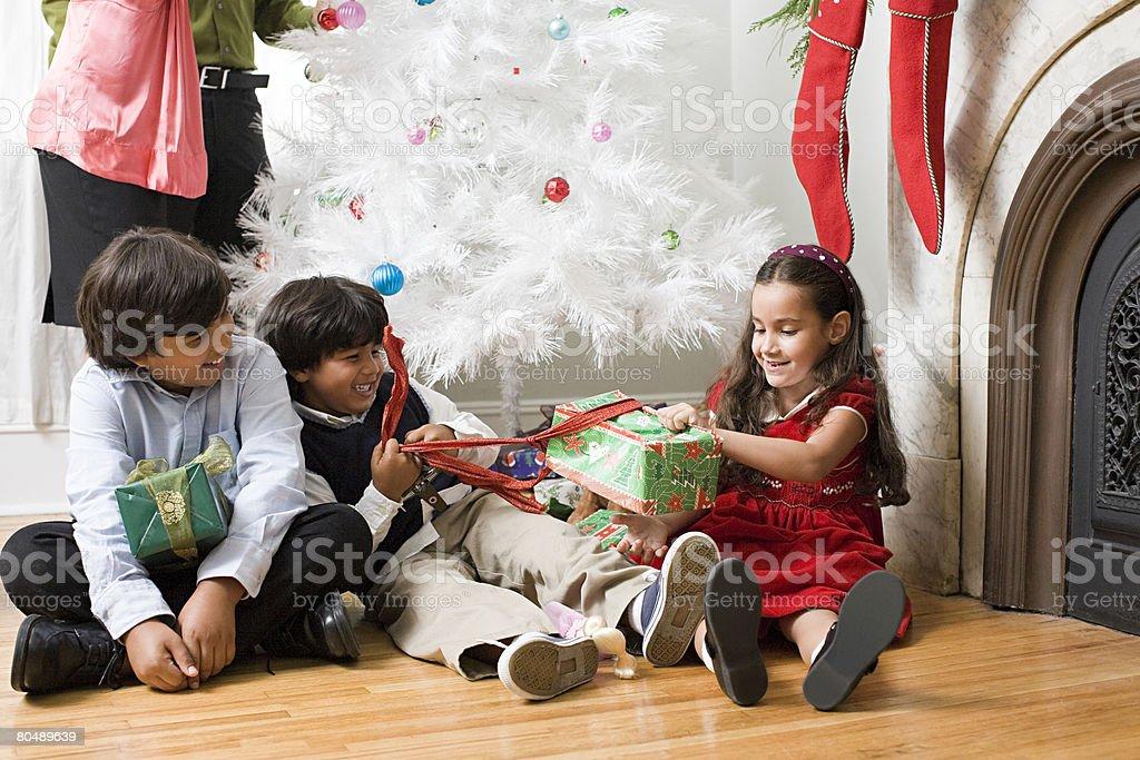 Filhos abrindo os presentes foto de stock royalty-free