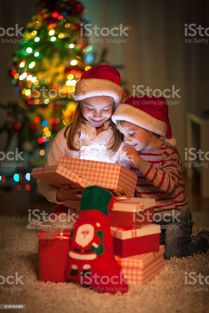 Children opening their Christmas gifts stock photo
