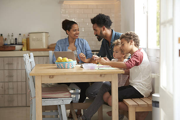 Children Paint At Kitchen Table As Parents Look At Laptop - Photo