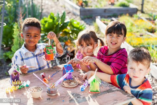 Multi-ethnic group of children (3 to 5 years) at community garden, painting bird feeders.