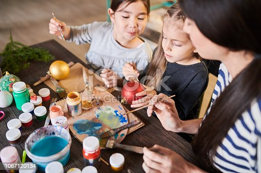 High angle portrait of two cute little girls painting Christmas baubles in crafting class with  teacher helping them