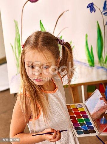 154371635istockphoto Children painting finger on easel. Group of kids with teacher. 826182376
