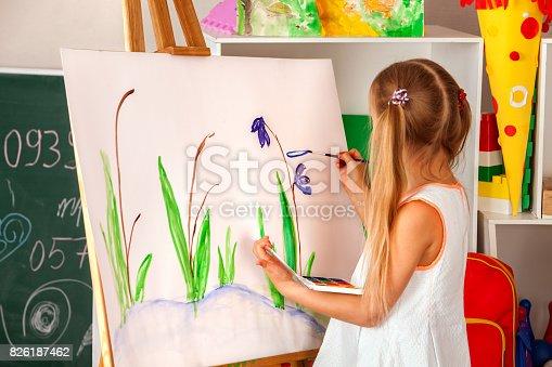 154371635istockphoto Children painting finger on easel. Group of kids with teacher. 826187462