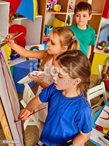 154371635istockphoto Children painting finger on easel. Group of kids with teacher. 826416222