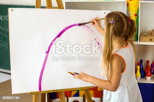 154371635istockphoto Children painting finger on easel. Group of kids with teacher. 826802194