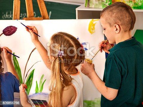 154371635istockphoto Children painting finger on easel. Group of kids with teacher. 826854756