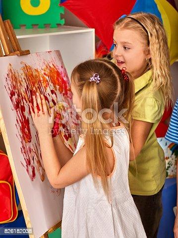 154371635istockphoto Children painting finger on easel in art class. 826182038