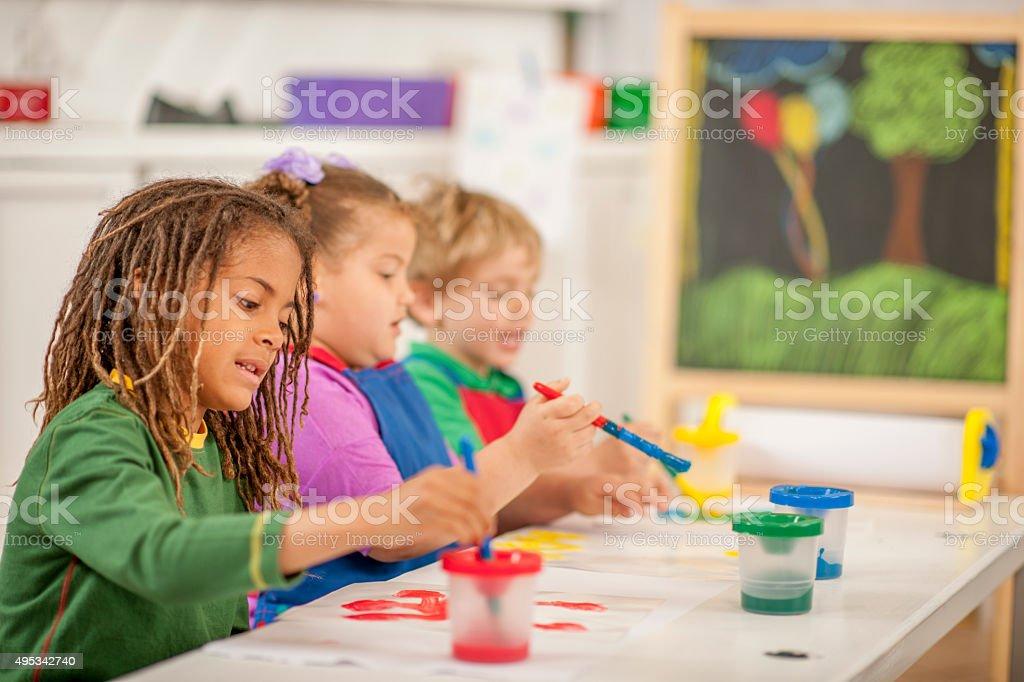 Fotografía de Los Niños Pintando Juntos En Clase y más banco de ...