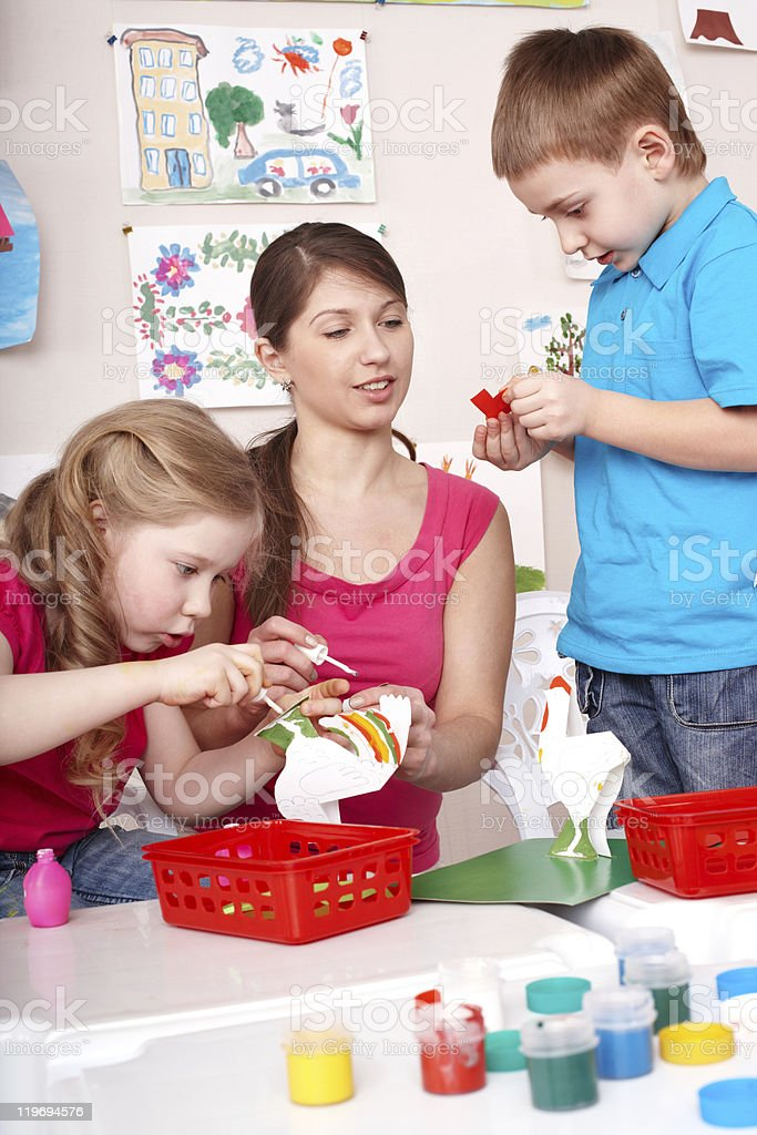 Children painting with teacher. royalty-free stock photo