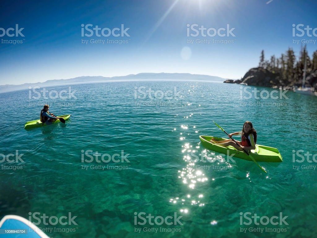 Kinder spielen und Kajak zusammen auf dem schöne, kristallklare Wasser des Lake Tahoe, Kalifornien, an einem sonnigen Sommertag. – Foto