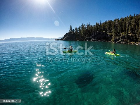 Children kayak and play in the beautiful clear waters of Lake Tahoe, California on a beautiful summer morning