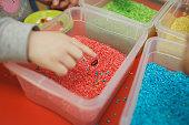 istock Children play educational games with a sensory bin in kindergarten 1198448139