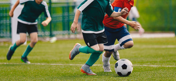 Children Play Football Tournament Game. Young Boys Running and Kicking Football Ball on Grass Sports Field Children Play Football Tournament Game. Young Boys Running and Kicking Football Ball on Grass Sports Field studded stock pictures, royalty-free photos & images