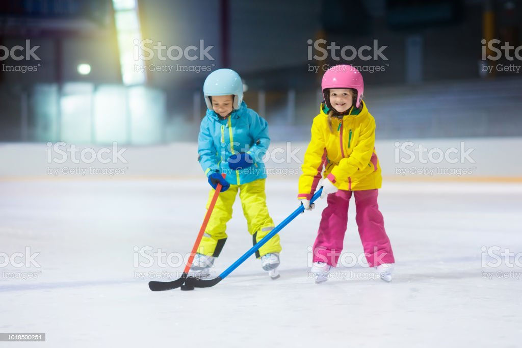 Children play ice hockey on indoor rink. Healthy winter sport for...
