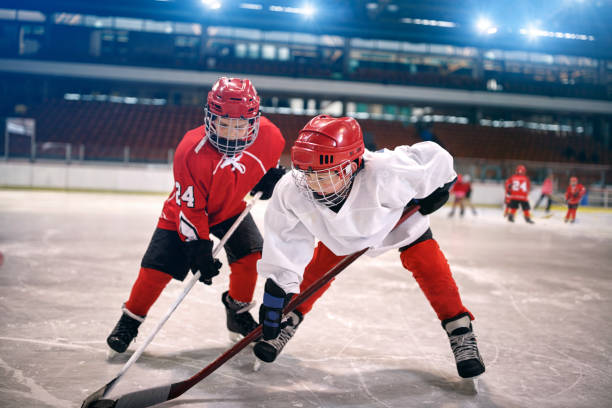 children play ice hockey - hockey stock pictures, royalty-free photos & images