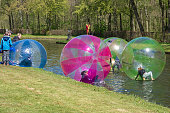 Haarzuilens, Netherlands – April 24, 2016: Children play in large plastic balls on the pond of the park