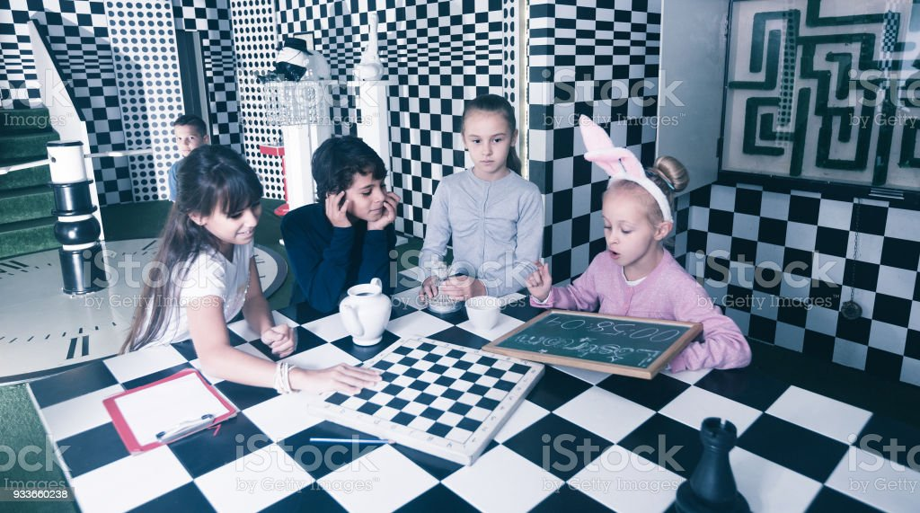 children play in the chess quest room stock photo