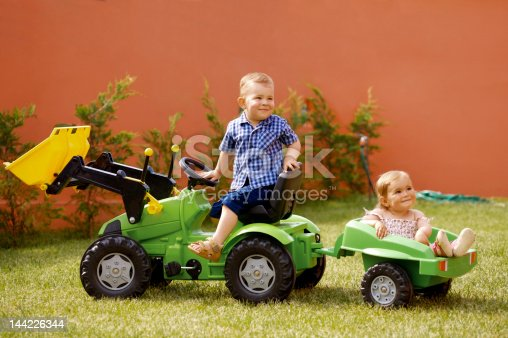 One and two years old babies play in the garden with a toy tractor.