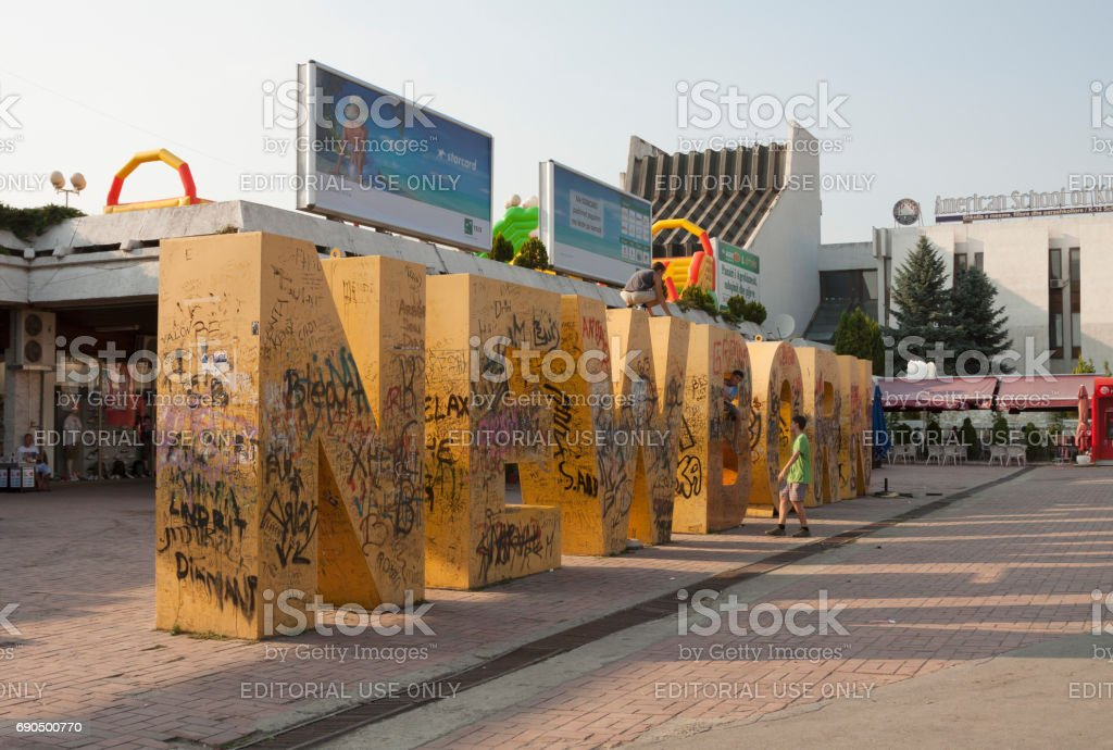 Children play on Newborn monument of independence in the center of Pristina, capital of Kosovo stock photo