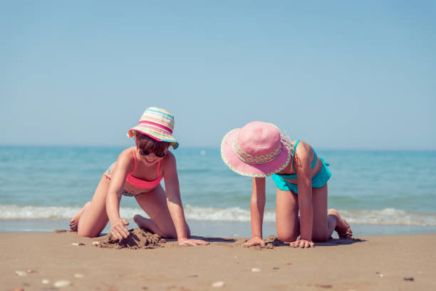 children play on the beach - little girl picking up sea shells at the beach stock pictures, royalty-free photos & images