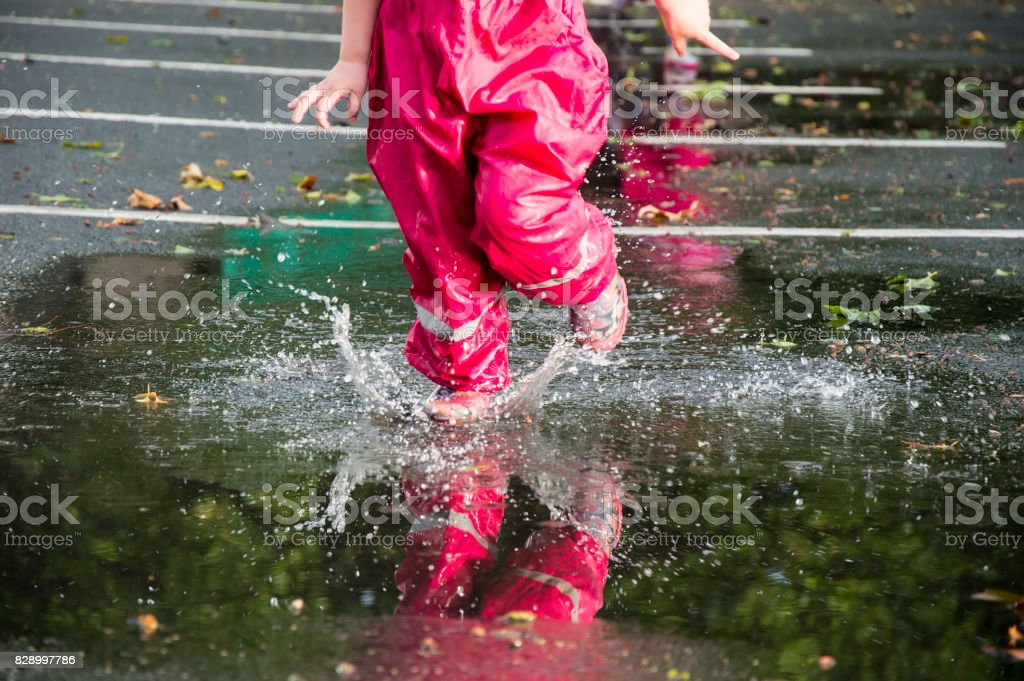 Children play on the street after the rain in pink bright rubber...