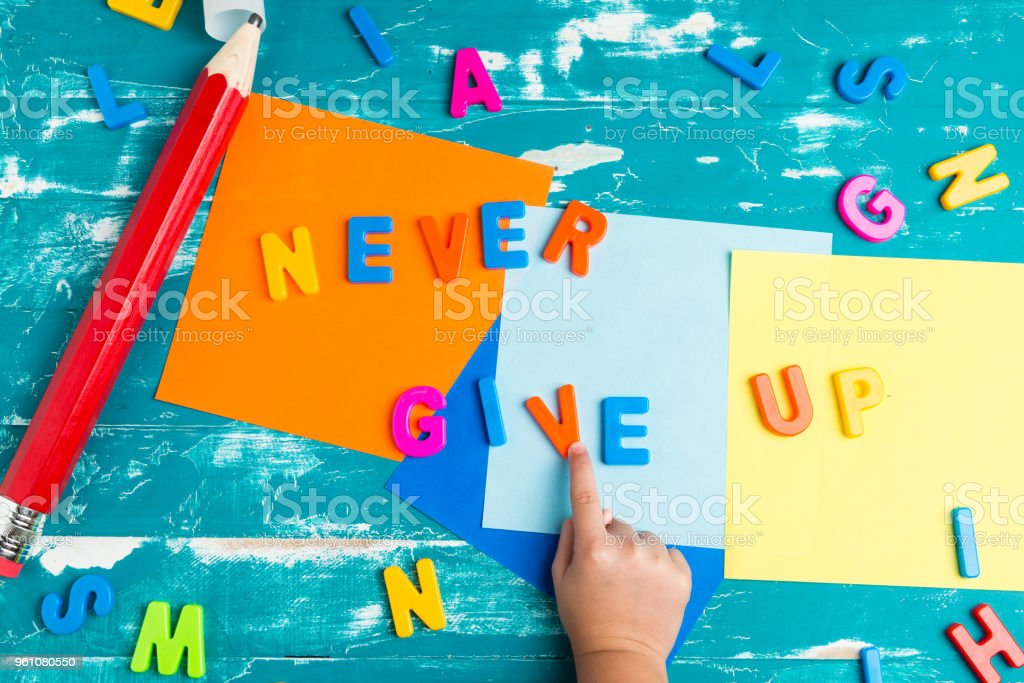 Children play plastic letters to combinations word 'NEVER GIVE UP' . stock photo