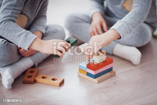 470874196istockphoto Children play with a toy designer on the floor of the children's room. Two kids playing with colorful blocks. Kindergarten educational games 1136782910