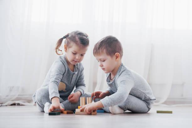 Kinder spielen mit einem Spielzeugdesigner auf dem Boden des Kinderzimmers. Zwei Kinder, die mit bunten Blöcken spielen. Kindergartenpädagogische Spiele – Foto