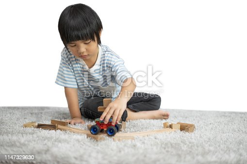 470874196istockphoto Children play with a toy designer on the floor of the children's room. Kids playing with colorful blocks. Kindergarten educational games isolated on white background. 1147329630