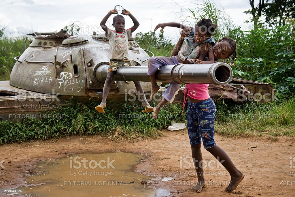 Children play with an abandoned tank. stock photo