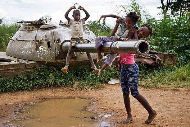 As crianças brincam com um tanque abandonado. - foto de acervo