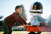 Three boys have fun pretending they are astronauts, wearing a space helmet while they take turns pulling each other in a red wagon.  Childhood imagination and play at its best.